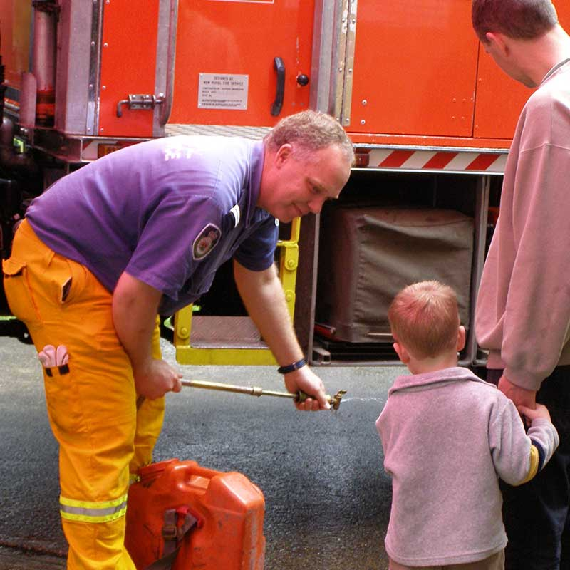 Fireman showing child and parent his fire truck